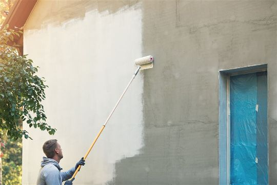 Rolling paint on a commercial exterior painting job in Rio Rancho New Mexico
